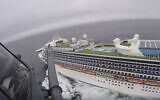 In this image from video, provided by the California National Guard, a helicopter carrying airmen with the 129th Rescue Wing flies over the Grand Princess cruise ship off the coast of California, March 5, 2020. (California National Guard via AP)