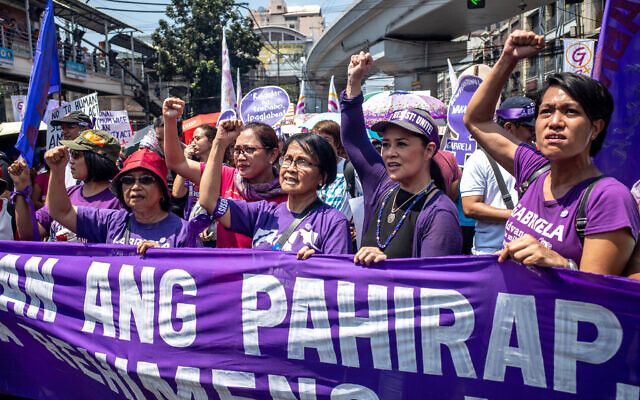 Leaders of various women's groups raise their fists as they march near the Malacanang presidential palace to mark International Women's Day, March 8, 2020, in Manila, Philippines. (AP Photo/Iya Forbes)