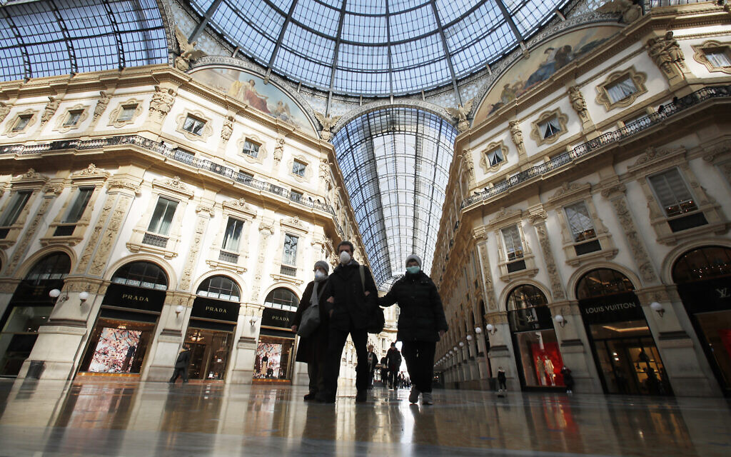 People wear masks as they walks inside Vittorio Emanuele II gallery, in downtown Milan, Italy, Sunday, March 8, 2020. (AP/Antonio Calanni)
