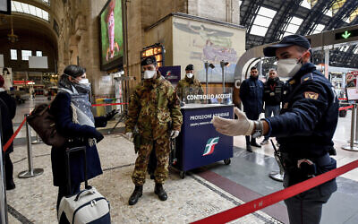 Police officers and soldiers check passengers leaving from Milan main train station, Italy, March 9, 2020 (Claudio Furlan/LaPresse via AP)