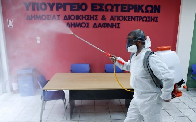 """A worker wearing a protective suit sprays disinfectant inside a citizen's service office in the Athens' eastern suburb of Dafni, March 9, 2020. The sign reads """"Interior Ministry. Municipality of Dafni."""" (Thanassis Stavrakis/AP)"""
