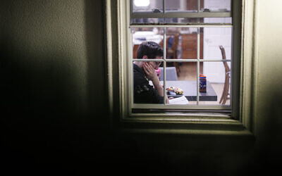 A self-quarantined resident who claims to have tested positive for COVID-19 listens beside his window as volunteers perform a Purim reading from the Book of Esther, Monday, March 9, 2020, in New Rochelle, N.Y. (AP/John Minchillo)