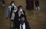 Passengers wear masks at Ben Gurion Airport near Tel Aviv, Israel, March 10, 2020 (AP Photo/Ariel Schalit)