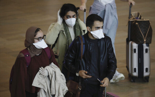 Passengers wearing masks to help protect against coronavirus arrive at Ben Gurion Airport near Tel Aviv, Tuesday, March 10, 2020. (AP Photo/Ariel Schalit)