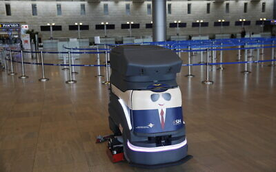 A robot cleans the hall of empty check-in counters at the Ben Gurion Airport near Tel Aviv, Israel, Tuesday, March 10, 2020.  (AP/Ariel Schalit)