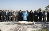 Mourners wearing face masks and gloves pray over the body of former politburo official in the Revolutionary Guard Farzad Tazari, who died Monday after being infected with the new coronavirus, at the Behesht-e-Zahra cemetery just outside Tehran, Iran, March 10, 2020 (Mahmood Hosseini/Tasnim News Agency via AP)