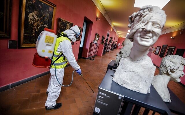 A worker sprays disinfectant as sanitization operations against Coronavirus are carried out in the museum hosted by the Maschio Angioino medieval castle, in Naples, Italy, March 10, 2020. (Alessandro Pone/LaPresse via AP)