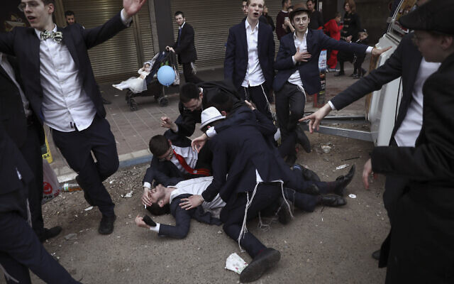 Jewish ultra-Orthodox men celebrate the Jewish festival of Purim in Bnei Brak, Israel, Tuesday, March 10, 2020.. (AP/Oded Balilty)