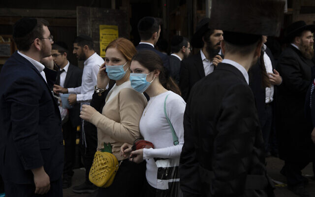 Jewish ultra-Orthodox girls wear face masks during celebrations of the Jewish festival of Purim in Bnei Brak, Israel, Tuesday, March 10, 2020. (AP/Oded Balilty)