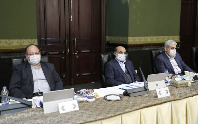 In this photo released by the official website of the office of the Iranian Presidency, cabinet members wearing face masks attend their meeting in Tehran, Iran, Wednesday, March 11, 2020. (Iranian Presidency Office via AP)