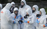 Workers from a Servpro disaster recovery team wearing protective suits and respirators are given supplies as they line up before entering the Life Care Center in Kirkland, Washington, to begin cleaning and disinfecting the facility, March 11, 2020. (AP Photo/Ted S. Warren)