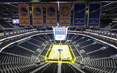 In this Aug. 26, 2019, file photo, the Golden State Warriors championship banners hang above the seating and basketball court at the Chase Center in San Francisco (AP Photo/Eric Risberg, File)