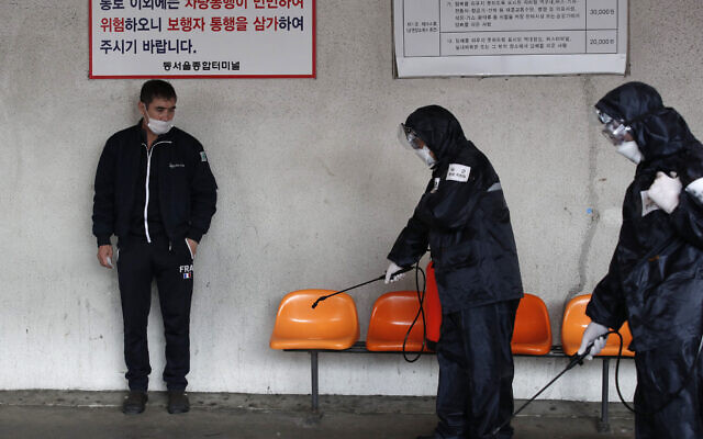 A passenger, left, stands as the members of reserved forces units wearing protective gears disinfect chairs as a precaution against the new coronavirus at a bus terminal in Seoul, South Korea, March 12, 2020 (AP Photo/Lee Jin-man)