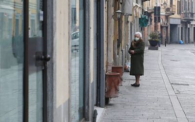In this photo taken March 12, 2020, an elderly woman wearing a mask waits to enter a deli meat and cold cuts shop in Codogno, Italy. The northern Italian town that recorded Italy's first coronavirus infection has offered a virtuous example to fellow Italians, now facing an unprecedented nationwide lockdown. (AP Photo/Antonio Calanni)