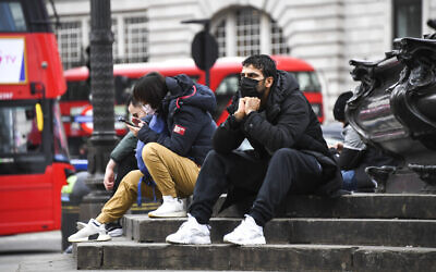 People wear face masks as they sit on the Shaftesbury Memorial Fountain in Piccadilly Circus, in London, March 13, 2020 (AP Photo/Alberto Pezzali)