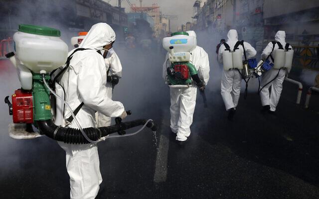 Firefighters disinfect a street against the new coronavirus, in western Tehran, Iran, March 13, 2020. (AP Photo/Vahid Salemi)