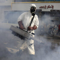 A firefighter disinfects a square against the new coronavirus, in western Tehran, Iran, March 13, 2020. (Vahid Salemi/AP)