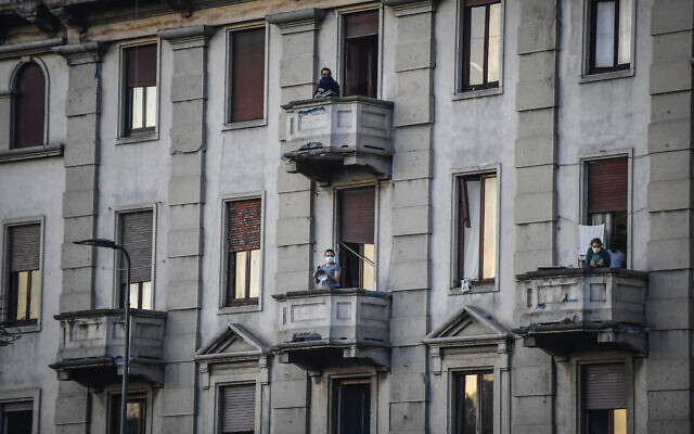 People lean out of their home's balconies to play and sing during a flash mob launched throughout Italy to bring people together and try to cope with the emergency of coronavirus, in Milan, Italy, March 13, 2020 (Claudio Furlan/LaPresse via AP)