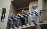 A man plays guitar on the balcony of his home during a flash mob launched throughout Italy to bring people together and try to cope with the emergency of coronavirus, in Milan, Italy,March 13, 2020 (AP Photo/Luca Bruno)