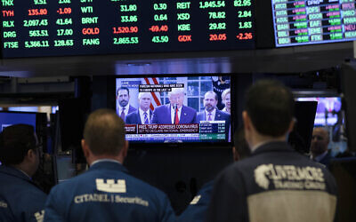Traders listen at the New York Stock Exchange to US President Donald Trump's televised speech from the White House, March 13, 2020, in New York. (AP Photo/Mark Lennihan)