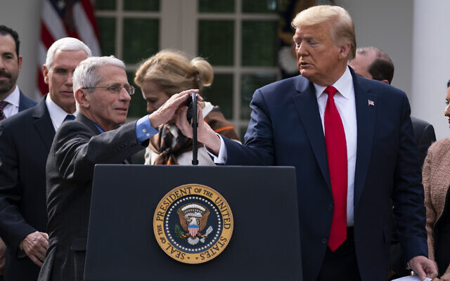 Dr. Anthony Fauci, director of the National Institute of Allergy and Infectious Diseases, adjusts the microphone to speak during a news conference on the coronavirus with US President Donald Trump in the Rose Garden at the White House, March 13, 2020, in Washington. (AP Photo/Evan Vucci)