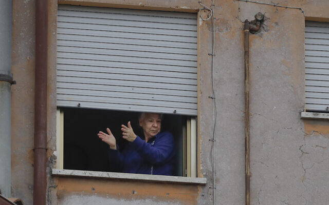A woman applauds from her window at the Garbatella neighborhood in Rome, March 14, 2020 (AP Photo/Alessandra Tarantino)