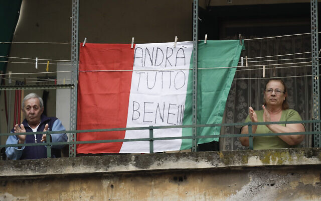 A couple applauds next to an Italian flag reading 'everything will be alright,' at the Garbatella neighborhood, in Rome, March 14, 2020 (AP Photo/Alessandra Tarantino)