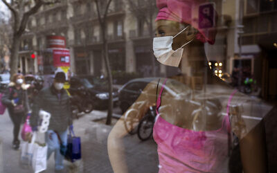 People wearing masks and carrying supplies walk past a mannequin wearing a mask in downtown Barcelona, Spain, March 14, 2020 (AP Photo/Emilio Morenatti)