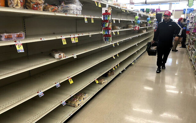 A shopper walks past empty shelves where bread is normally displayed in a supermarket, March 15, 2020, in Boston. (AP Photo/Steven Senne)