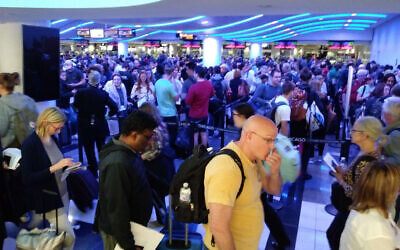 In this Saturday, March 15, 2020, photo, travelers wait in line to go through customs at O'Hare International Airport in Chicago.  (Michael Sadler via AP)