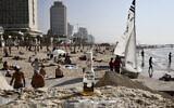 Israelis enjoy the beach in Tel Aviv, March 16, 2020. (AP Photo/Oded Balilty)