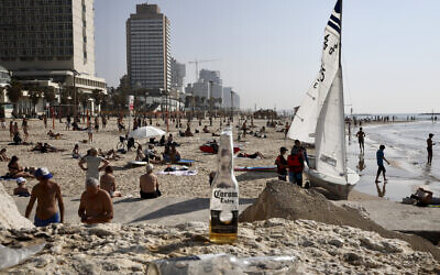 Israelis enjoy the beach in Tel Aviv, March 16, 2020. (AP Photo/Oded Balilty)