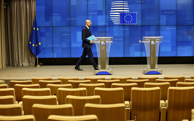 European Council President Charles Michel arrives to address a nearly empty press theater after a videoconference with G7 leaders at the European Council building in Brussels, March 16, 2020. (AP Photo/Olivier Matthys)
