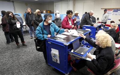 Chicago residents line up for early voting at the Roden Library Monday, March 16, 2020, in Chicago. (AP/Charles Rex Arbogast)