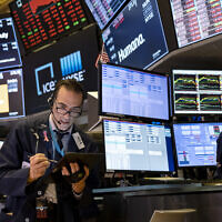 Illustrative: Trader Gregory Rowe works on the floor of the New York Stock Exchange at the end of the trading day, March 16, 2020. (AP/Craig Ruttle)