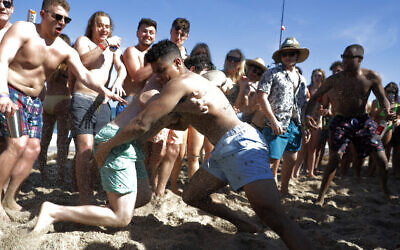 Two men wrestle each other as spring break revelers look on during a contest on the beach, March 17, 2020, in Pompano Beach, Florida (AP Photo/Julio Cortez)