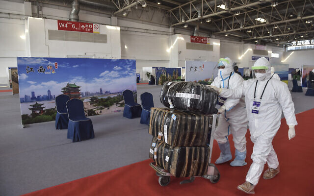Illustrative: In this March 17, 2020 photo released by China's Xinhua News Agency, workers in protective suits push a cart with passengers' luggage at the New China International Exhibition Center, which has been converted into a facility to screen international flight passengers arriving in Beijing.  (Peng Ziyang/Xinhua via AP)