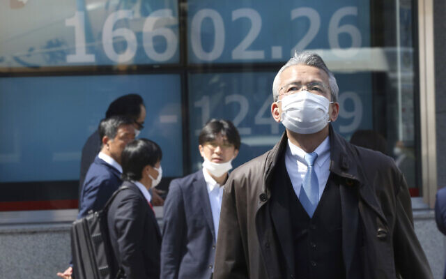 People walk by an electronic stock board of a securities firm in Tokyo, March 19, 2020 as shares in Asia failed to hold onto opening gains. (AP Photo/Koji Sasahara)