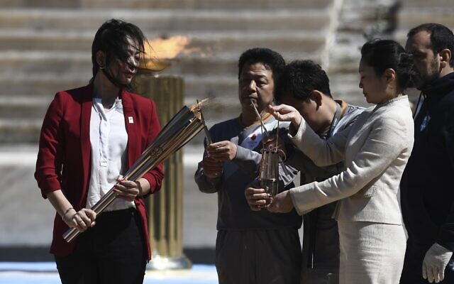 Former Japanese swimmer Imoto Naoko holds the Olympic torch during the Olympic flame handover ceremony for the 2020 Tokyo Summer Olympics, in Athens, March 19, 2020.(Aris Messinis/Pool via AP)