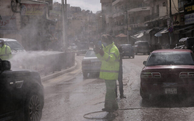 An employee of the Greater Amman Municipality sanitizes vehicles at one of their stations, amid concerns over the coronavirus pandemic, in Amman, Jordan, March 19, 2020. (AP Photo/Raad Adayleh)