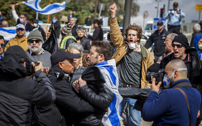 """Israeli police officers scuffle with a man during a protest to """"save democracy"""" outside the Knesset in Jerusalem, March 19, 2020. (AP Photo/Eyal Warshavsky)"""