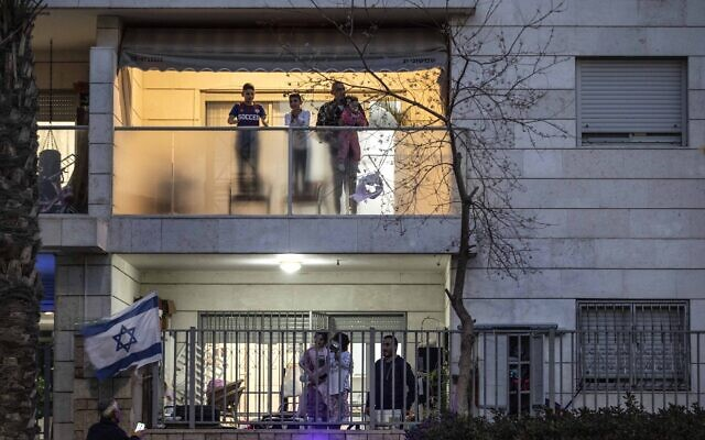 Israeli families stand on their balconies and applaud medical teams fighting the coronavirus outbreak in the town of Ashkelon, March 19, 2020. (AP Photo/Tsafrir Abayov)