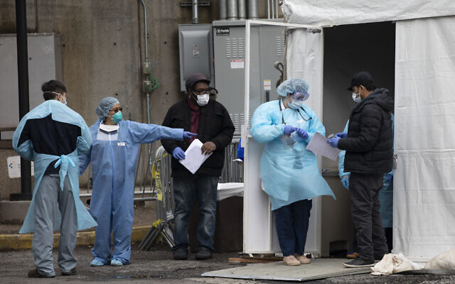 Hospital personnel assist people at a coronavirus screening tent outside the Brooklyn Hospital Center, March 19, 2020, in New York. (Mark Lennihan/AP)