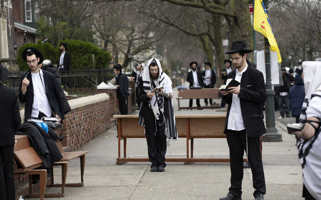 Orthodox Jewish men use 'social distancing' as they pray outside the Chabad Lubavitch World Headquarters, March 20, 2020, in the Brooklyn borough of New York, before leaders of six major organizations released a joint statement urging worshipers to 'avoid, to the maximum extent feasible, any outside interactions' to help stop the coronavirus pandemic. (AP Photo/Mark Lennihan)