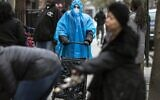 A woman dressed in a poncho, face mask and protective eyewear pushes her grocery cart in the Bedford-Stuyvesant neighborhood of Brooklyn, New York, on Friday, March 20, 2020. New York Gov. Andrew Cuomo is ordering all workers in non-essential businesses to stay home and banning gatherings statewide. Nonessential gatherings of individuals of any size or for any reason are canceled or postponed. (AP Photo/Wong Maye-E)