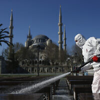 A municipality worker wearing a face mask and protective suits disinfects chairs outside the the historical Sultan Ahmed Mosque, also known as Blue Mosque, amid the coronavirus outbreak, in Istanbul, March 21, 2020 (AP Photo/Emrah Gurel)