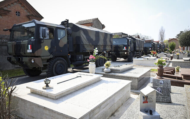 A convoy of Italian Army trucks arrives from Bergamo carrying bodies of coronavirus victims to the cemetery of Ferrara, Italy, where they will be cremated, Saturday, March 21, 2020. (Massimo Paolone/LaPresse via AP)