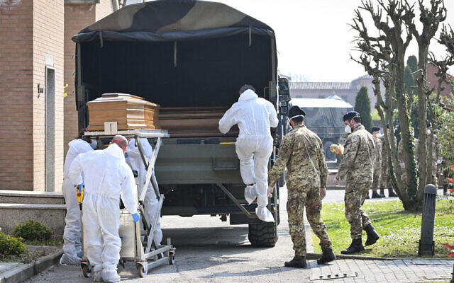 A convoy of Italian Army trucks is unloaded upon arrival from Bergamo carrying bodies of coronavirus victims to the cemetery of Ferrara, Italy, where they will be cremated, Saturday, March 21, 2020. The transfer was made necessary since Bergamo mortuary reached maximum capacity. For most people, the new coronavirus causes only mild or moderate symptoms. For some it can cause more severe illness, especially in older adults and people with existing health problems. (Massimo Paolone/LaPresse via AP)
