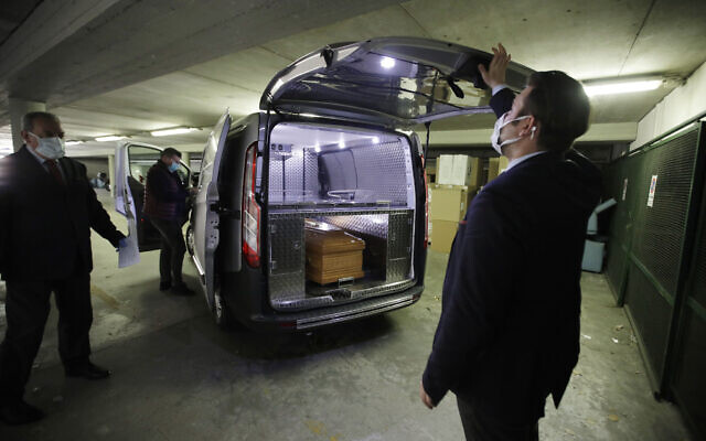 An employee of the San Giuseppe funeral agency, closes the mortuary van containing the coffin of Concetta Schifano, 73, who died of the Coronavirus, at the Multimedica hospital morgue, in Milan, Italy, Saturday, March 21, 2020. (AP Photo/Luca Bruno)