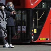 Women wearing masks walk past a bus in London, March 22, 2020. (Kirsty Wigglesworth/ AP)